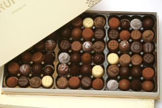 Image shows a 72-piece box of assorted Teuscher's chocolate truffles on a white background.