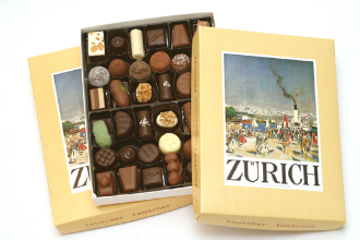 Image shows a yellow Lake Zurich box filled with assorted pieces of chocolate on a white background.