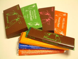 Image shows a variety of sizes and flavors of Teuscher Chocolate Bars on a white background.